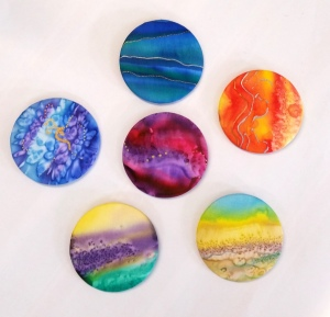 a selection of stunning brooches in watercolour technique, some with salt texturing and decorative additions of gutta embellishment.